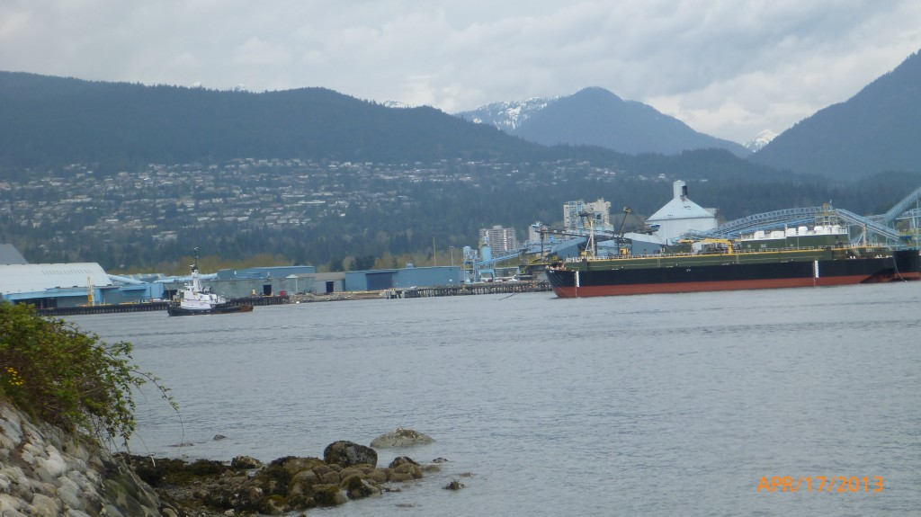 Tug boat pulling cargo and view of North Vancouver