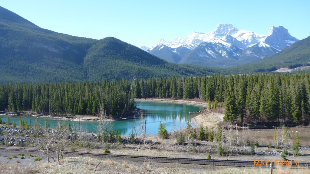 The changing terrain along the aqua colored bow river - mountains, green treed area and sparse brown land