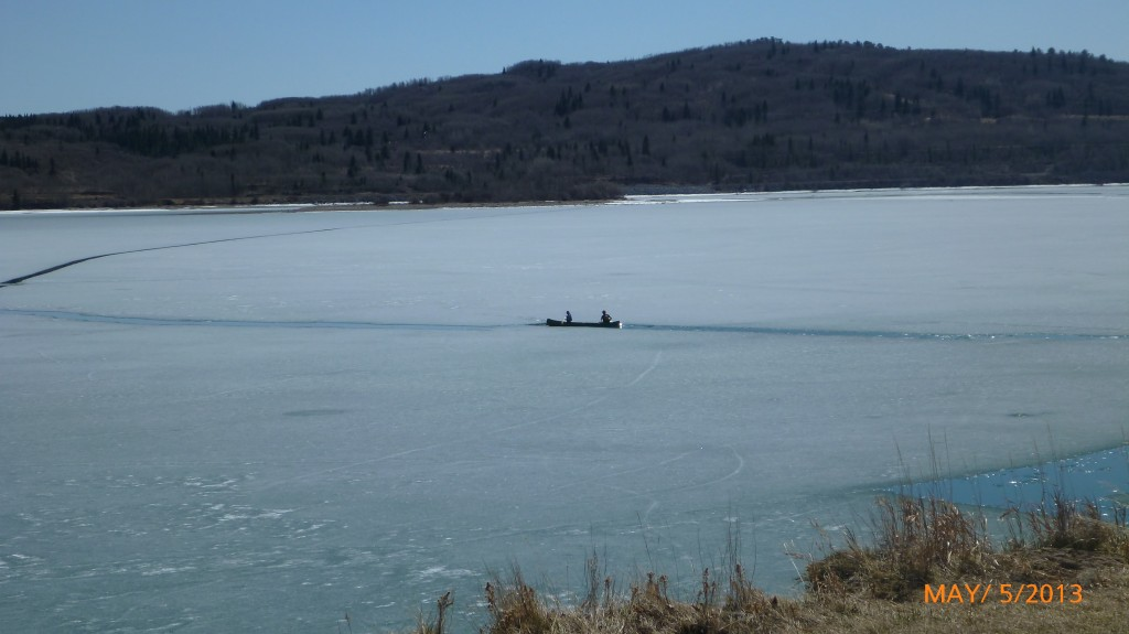Two canoeists navigating a small channel in the iced over lake