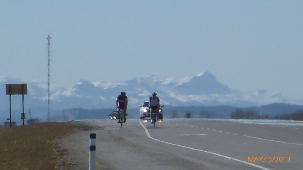 Cyclists outside of Cochrane with the mountains in the background